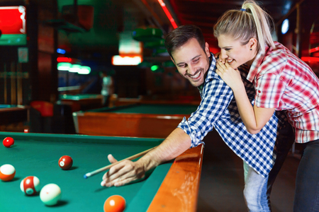 Couple drinking beer playing snooker on date