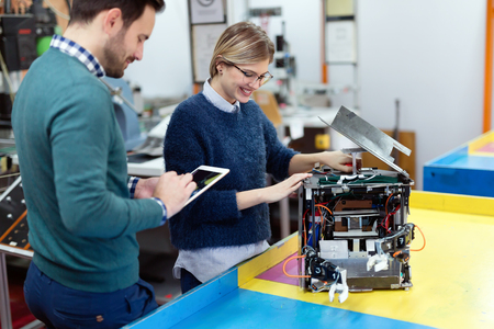 Young students of robotics preparing robot for testing Stockfoto