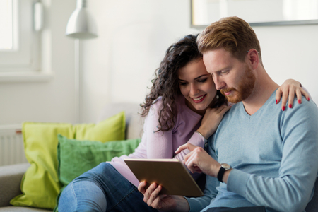 Pareja joven usando tableta digital en casa