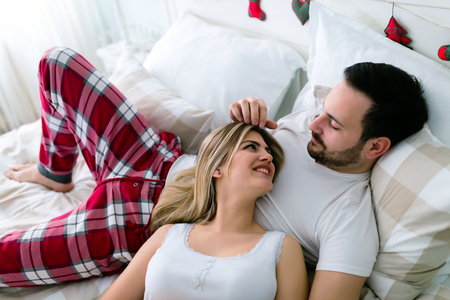 Young attractive couple having romantic time in bed Stock fotó