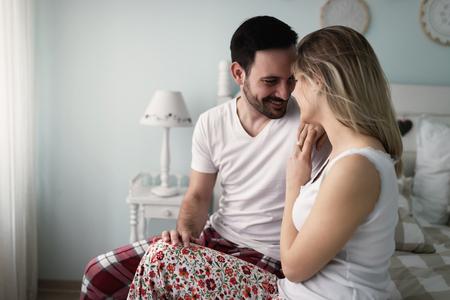 ベッドでロマンチックな時間を持つ若い魅力的なカップル 写真素材