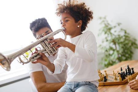 Mädchen mit ihrem Vater , der Trompete lernt Standard-Bild - 92912411