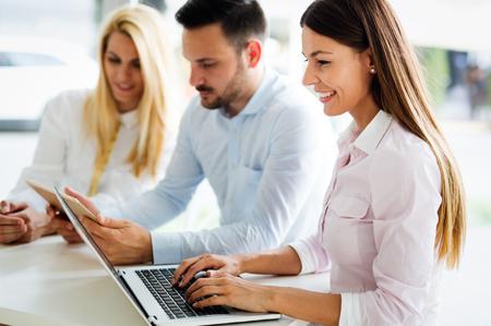 Tre giovani colleghi sorridenti che lavorano insieme sul computer portatile Archivio Fotografico