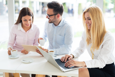 Three young smiling colleagues working together on laptop Stock Photo