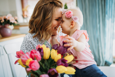 Child daughter congratulates moms and gives her flowers Banco de Imagens
