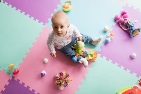 Baby toddler playing color toys at home or nursery