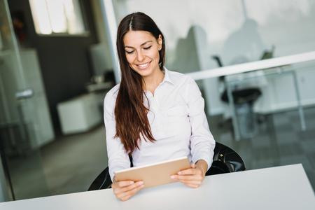 Nachdenkliche Geschäftsfrau , die Tablette im Büro hält Standard-Bild