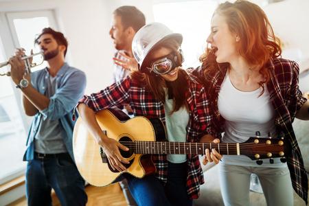 Jovens garotas dançando feliz tocando violão e festas