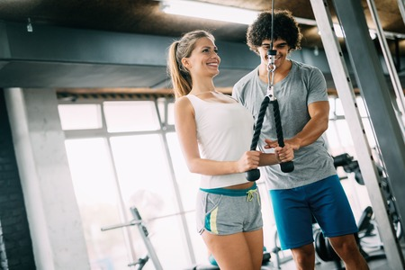 Beautiful girl working out with personal trainer Stock Photo
