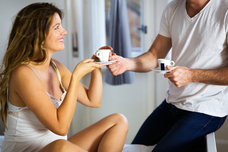 Handsome man bringing cup of coffee to his wife