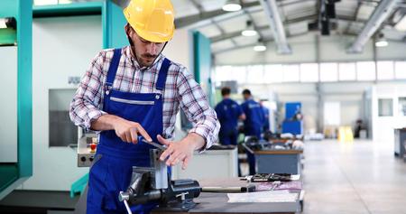 Industry Worker entering data in CNC machine at factory Zdjęcie Seryjne