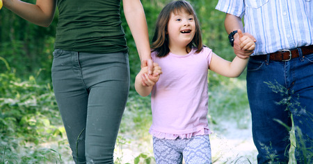 Beautiful little girl with down syndrome walking with parents Stock Photo