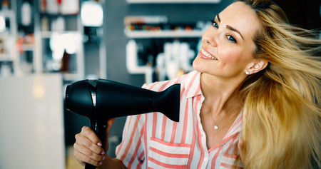 Portrait of beautiful young woman drying hairstyle Stock Photo
