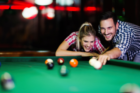 Young couple playing snooker together in bar Stock Photo