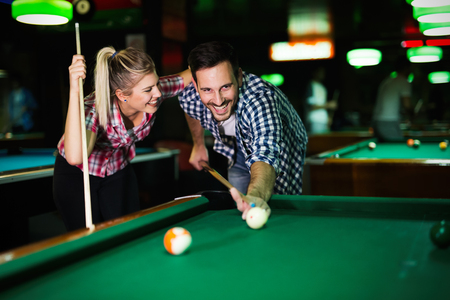 Young couple playing snooker together in bar Banque d'images