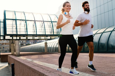 Young fitness couple running in urban area Stock Photo