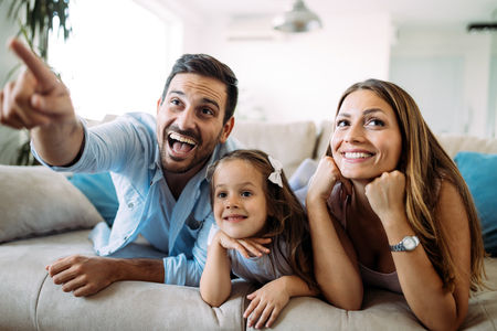 Happy family watching television at their home Stockfoto