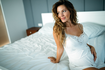 Portrait of attractive pregnant woman sitting on bed