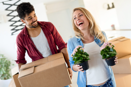 home, people, moving and real estate concept - happy couple having fun while moving in Stockfoto