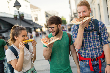 Happy group of people eating pizza outdoors Stock Photo