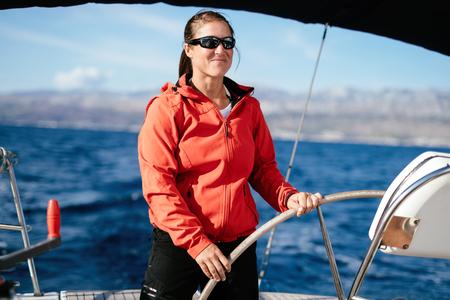 彼女のボートで航海する魅力的な強い女性