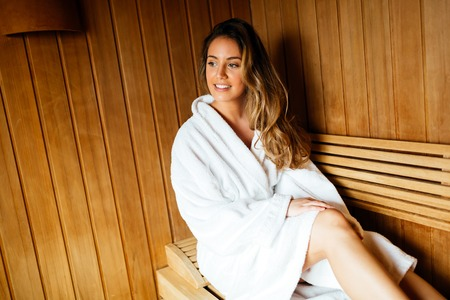Beautiful woman relaxing in finnish sauna 版權商用圖片