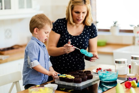 Child helping mother make cookies Stock Photo