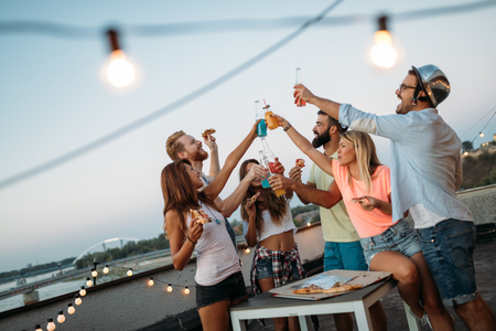 Friends having fun and drinking outdoor on a rooftop get together
