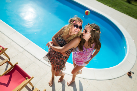 Happy girls smiling by the pool and enjoying summer Stock Photo