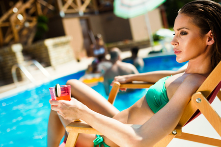Woman relaxing and sun tanning by the swimming pool Stock Photo - 101056728