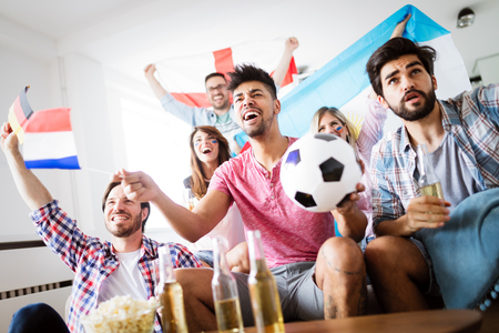 Friends watching football game at home Banque d'images