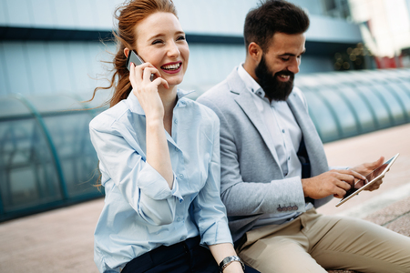 Business man and woman working outdoors with tablet computer in front of office Stock Photo