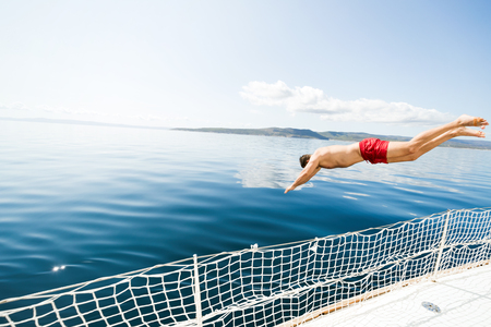 Young man jumping off boat into water 写真素材