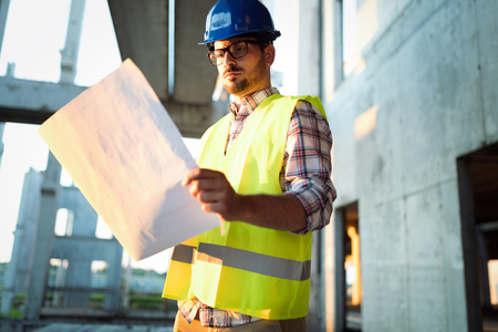 Portrait of male site contractor engineer with hard hat holding blue print paper Stockfoto