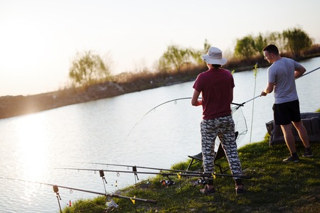 Young man fishing on a lake at sunset and enjoying hobby