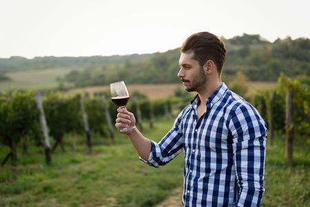 Winegrower tasting wine in vineyard