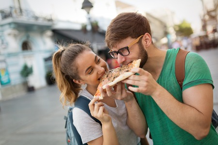 Happy students eating pizza on street