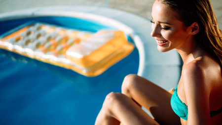 Woman relaxing and sun tanning by the swimming pool Stock Photo