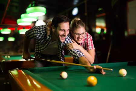 Young couple playing snooker together in bar 스톡 콘텐츠