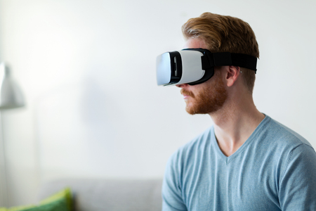 Man wearing virtual reality headset at home