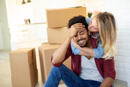 Tired couple with boxes moving into new home