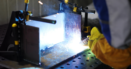 Worker cutting metalsheet by torch with bright sparks in fabication factory Stock Photo