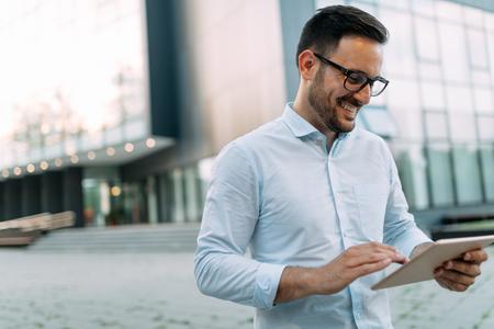 Portret van zakenman die in glazen tablet houden