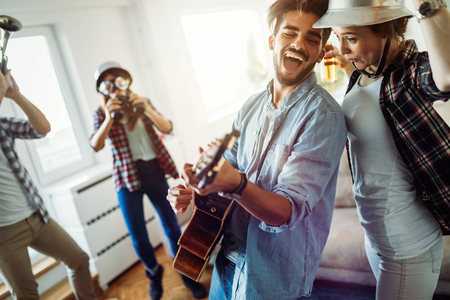 Group of friends playing guitar and partying at home Stock Photo