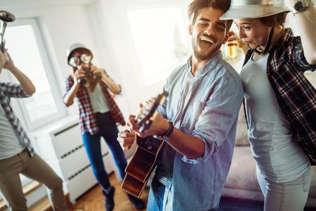 Grupo de amigos tocando la guitarra y de fiesta en casa