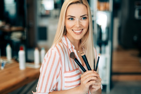 Portrait of the beautiful woman with make-up brushes near attractive face Stock Photo
