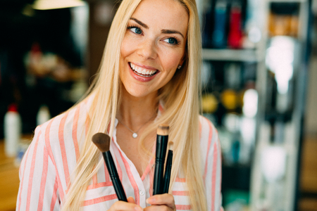 Portrait of the beautiful cute woman with make-up brushes