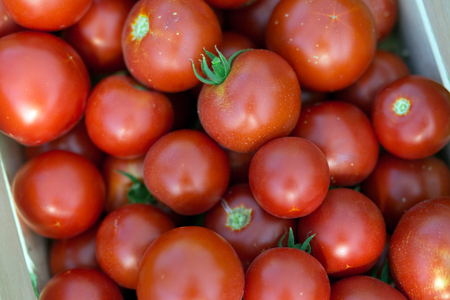 Picture of many tomatoes in wooden crate