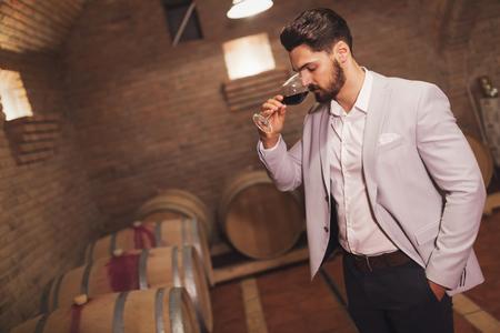 Oenologist tasting wines in cellar Фото со стока