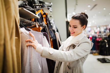 Młoda atrakcyjna kobieta kupuje ubrania w centrum handlowym